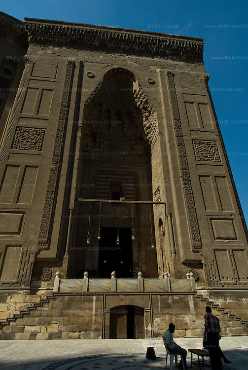 Cairo, Egypt -- The entrance to the Sultan Hassan mosque dwarfs a local backgammon game. © Rick Collier / RickCollier.com.