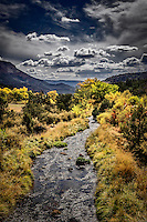 The Jemez River flows through an autumn landscape under a stormy sky just north of Jemez Springs, New Mexico.