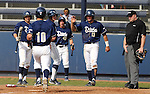 UC Davis Aggies greet Izaak Silva at the plate after Evan Heptig hit a three-run double in a college baseball game between the Washington Huskies in Davis, Ca., on Saturday, Feb. 16, 2013. Davis won the opener 6-5 and dropped the second game 3-2..Photo by Cathleen Allison