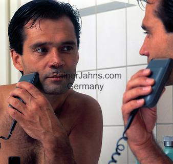 Mann mit nacktem Oberkoerper vorm Spiegel rasiert sich mit Trockenrasierer   man with electric razor, looking into mirror