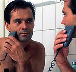 Mann mit nacktem Oberkoerper vorm Spiegel rasiert sich mit Trockenrasierer | man with electric razor, looking into mirror