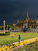 A young Girl is feeding pigeons and a Storm approaching over the Grand Performance Hall at the Grand Palace in Phnom Penh, Cambodia.