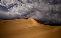 Storm clouds pass over Eureka Dunes at Death Valley National Park, California