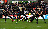 Wednesday, 01 January 2014<br /> Pictured: Ashley Williams of Swansea (C) takes a shot off target.<br /> Re: Barclay's Premier League, Swansea City FC v Manchester City at the Liberty Stadium, south Wales.