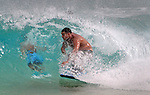 A boarder sails by another person who is tuck in a wave at Sandy Beach in Hawaii.