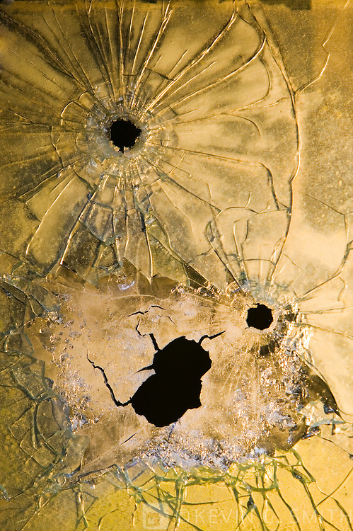 Bullett holes in window pane of an old World War II Quonset Hut abandonded on Long Island off the coast of Kodiak, Alaska USA.