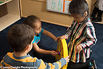 Preschool 3-4 year olds group of two girls and boy playing with toy clock