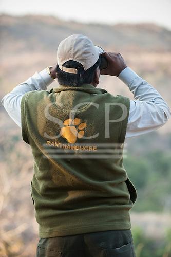 Rajasthan, India. Ranthambore National Park. Ranger with cap  binoculars and tiger footprint vest.