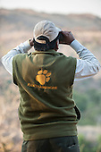 Rajasthan, India. Ranthambore National Park. Ranger with cap  binoculars and tiger footprint vest.