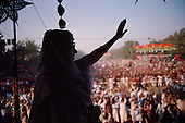Punjab, Pakistan<br /> November 11, 1988<br /> <br /> Benazir Bhutto campaigns in the Punjab Province.<br /> <br /> Benazir Bhutto is the eldest child of former Pakistan President and Prime Minister Zulfikar Ali Bhutto. She found herself placed under house arrest in the wake of her father's imprisonment and subsequent execution in 1979. In 1984 she became the leader in exile of the Pakistan Peoples Party (PPP), her father's party, though she was unable to make her political presence felt in Pakistan until after the death of General Muhammad Zia-ul-Haq. <br /> <br /> On 16 November 1988 Benazir's PPP won the largest bloc of seats in the National Assembly. Bhutto was sworn in as Prime Minister in December, at age 35 she became the first woman to head the government of a Muslim-majority state in modern times. <br /> <br /> She was removed from office 20 months later under orders of then-president Ghulam Ishaq Khan for alleged corruption. Bhutto was re-elected in 1993 but was again removed by President Farooq Leghari in 1996, on similar charges. Bhutto went into self-imposed exile in Dubai in 1998, until she returned to Pakistan on October 2007, after General Musharraf granted her amnesty and all corruption charges withdrawn.