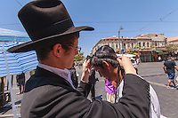 Israel,Jerusalem, an orhodox jude boy is putting the Tefillin to another boy before the pray