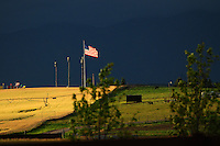 The American flag flies over the motor speedway in Kalispell, Montana. The sun lights up the flag against a dark storm cloud background. Bright yellow canola is in the foreground