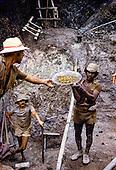 Serra Pelada gold mine, Brazil. Gold panning; garimpeiro holding a pan full of gold. Para State.