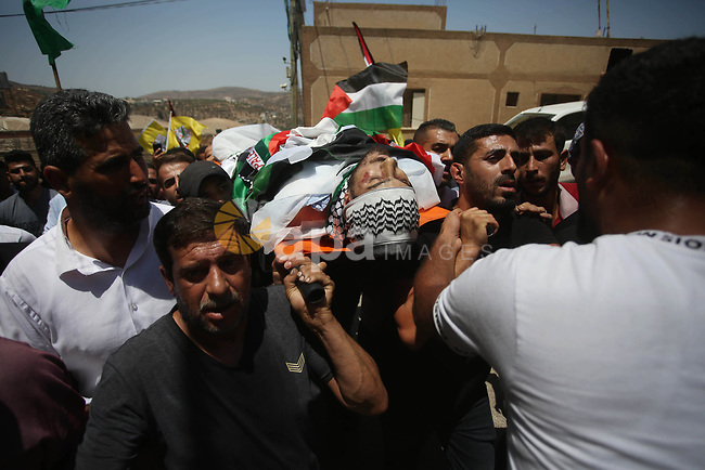 """Mourners attend the funeral of Palestinian Mohammad Fareed Hasan, who was killed by Israeli gunfire, in the village of Qusra near the city Nablus on August 4, 2021, after Israel handed over his body today. A Palestinian man was killed by Israeli gunfire in the West Bank on July 3 Palestinian authorities said, in an incident Israel's army described as a """"violent confrontation"""" between Palestinians and Jewish settlers. Photo by Shadi Jarar'ah"""