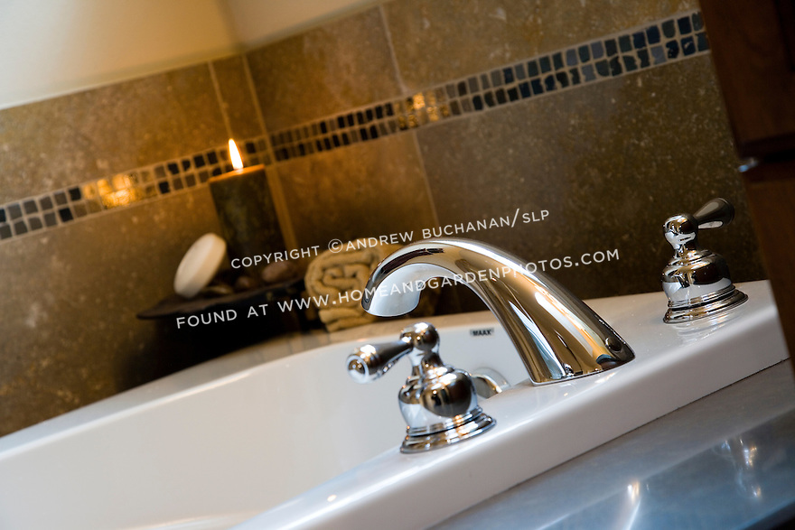 Close up detail image of a faucet waiting to spill water into a large soaking tub with a candle glowing behind in this tempting, relaxing vignette in a contemporary-styled master bath MBA featuring geometric decorative tile work and and plenty of natural light.
