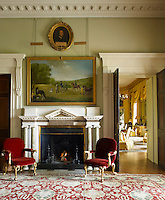 A pair of red velvet armchairs flanks a glowing fire in the entrance hall with a view into the drawing room