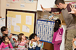 Education Preschool 3-4 year olds circle time group of children with two staff members counting activity