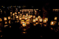 Individuals surrounded by hundreds of floating paper lanterns at the annual bon dance and Toro Nagashi (ìfloating lanterns set out to seaî) ceremony in Haleiwa. Inscribed with the names of the departed, the lanterns ride the outgoing tide to greet v