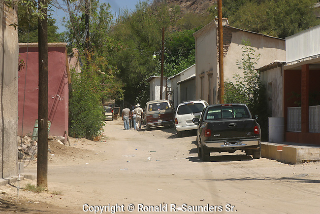 MEXICAN WORKERS WALK THROUGH DIRT ROAD on THEIR WAY to WORK