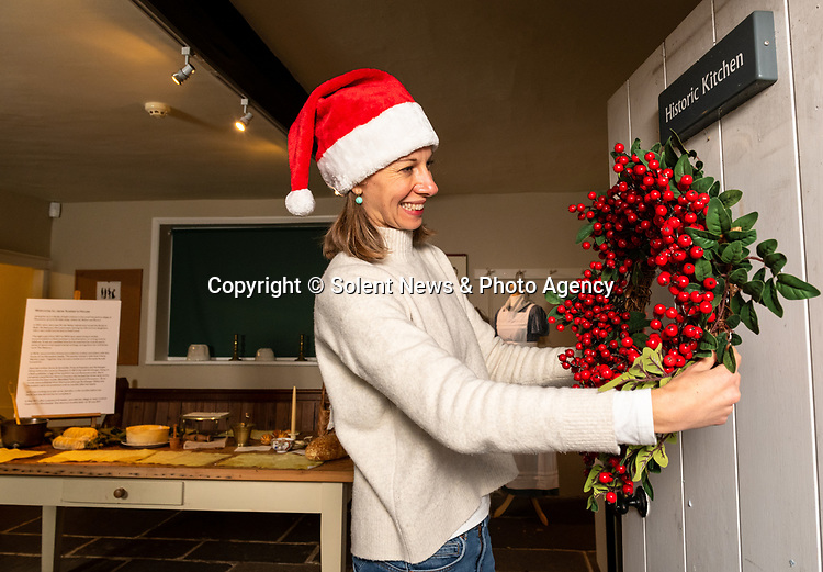 Pictured: Collections manager Sophie Reynolds hangs a Christmas wreath on the door of the historic kitchen as part of the Christmas experience as the Jane Austen's House Museum prepares to reopen to the public for the second time this year. <br /> <br /> Dame Emma Thompson has come to the aid of Jane Austen's former home by providing the voice to a new online Christmas experience.<br /> <br /> From today fans of the novelist can hear the actor - who won an Oscar for her screenplay for the 1995 film adaptation Sense and Sensibility - read from some of her books and letters.<br /> <br /> The 61 year old has recorded eight tracks for the Jane Austen House museum, which showcase her 'dry wit and enjoyment' of yuletide traditions.<br /> <br /> This week staff at the House in Chawton, Hants, have been putting up Christmas decorations in the hope that they will be able to reopen on December 3 if restrictions are eased, so visitors can enjoy the experience first hand.  SEE OUR COPY FOR FULL DETAILS.<br /> <br /> © Jordan Pettitt/Solent News & Photo Agency<br /> UK +44 (0) 2380 458800