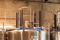 "A stainless steel fermentation tank with on top equipement for doing ""pigeage"". Pigeage means pushing down the ""cap"" of grape skins and other solid material that floats to the surface down into the must to get better extraction. Traditionally done by foot or with a hand tool, now done with hydraulic equipment. Each of the four black columns is a mechanical ""foot"".  Domaine E Guigal, Ampuis, Cote Rotie, Rhone, France, Europe"