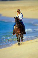 Young woman horseback riding on the beach