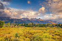 749450029 clouds from a clearing storm frame portions of the teton range with fall colored grasses in the foreground from blacktail ponds grand tetons national park wyoming