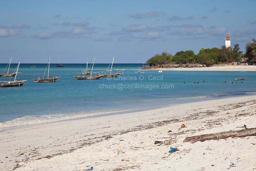 Nungwi, Zanzibar, Tanzania.  Beach, Fishing Boats in Harbor, Lighthouse in Background.