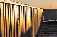 The setting sun casts soft glowing light and cast shadows on a wooden fishing pier on San Francisco Bay at the San Leandro Marina.