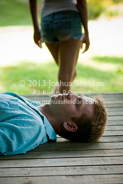 Young man laying down on porch with woman standing in back