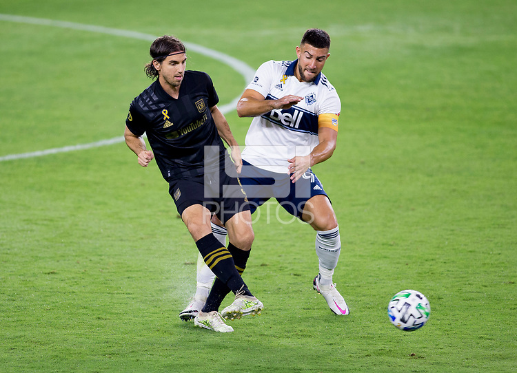 LOS ANGELES, CA - SEPTEMBER 23: Dejan Jakovic #5 of LAFC and Lucas Cavallini #9 of the Vancouver Whitecaps battle for a ball during a game between Vancouver Whitecaps and Los Angeles FC at Banc of California Stadium on September 23, 2020 in Los Angeles, California.