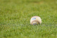 An ACC baseball sits in the grass behind home plate during the game between the Miami Hurricanes and the Wake Forest Demon Deacons at NewBridge Bank Park on May 25, 2012 in Winston-Salem, North Carolina.  The Hurricanes defeated the Demon Deacons 6-3.  (Brian Westerholt/Four Seam Images)