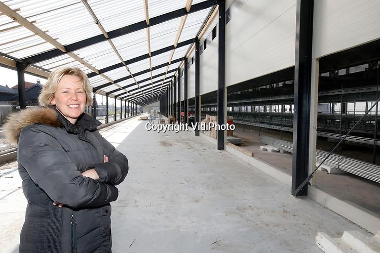 Foto: VidiPhoto<br /> <br /> BARNEVELD – In het buitengebied van Barneveld verrijzen op dit moment twee gloednieuwe kippenstallen van Pluimveebedrijf Beek. Het bedrijf met 39.000 kippen brandde vorig jaar juni af na blikseminslag. Beek was de eerste in Nederland met drie sterren Beter Leven, het keurmerk van de Dierenbescherming. Ook de ultra moderne en beter tegen brand beveiligde stallen (afzonderlijke warmtewisselaars) voldoen aan die hoogste normering. De schuren krijgen een zogenoemde overdekte bosrand. Op 14 mei arriveren de eerste van 40.000 kippen. De daken zijn voorzien van duizend zonnepanelen, waarmee het bedrijf zichzelf volledig van stroom kan voorzien. Beek, die ook een bouwbedrijf heeft, bouwt de stallen zelf. Foto: Eigenaresse Liza Beek.