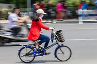 Yangzhou, Jiangsu, China.  Woman with Breathing Mask on Bicycle.