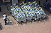 A woman with a shopping trolley outside a Lidl store in a retail park in Wembley, North London.