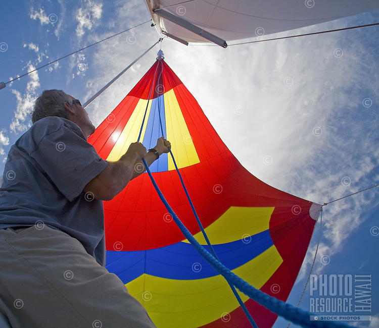 Crew of a cruising sailboat preparing to douse the spinnaker, during a Pacific crossing