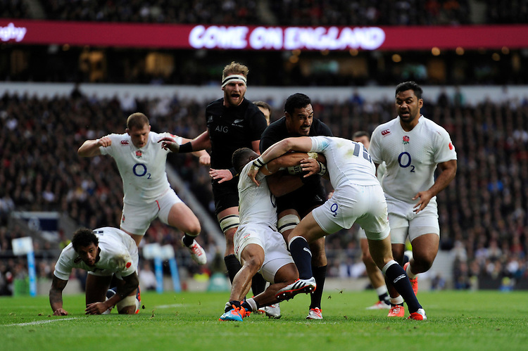Jerome Kaino of New Zealand is tackled by Kyle Eastmond and Mike Brown of England during the QBE International match between England and New Zealand at Twickenham Stadium on Saturday 8th November 2014 (Photo by Rob Munro)
