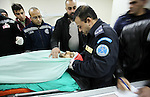 Members of the Palestinian police and medical staff inspect the body of a man who drove his car into Israeli forces in the village of Hawara near the West Bank city of Nablus before being shot dead earlier in the day on December 31, 2015. Photo by Nedal Eshtayah