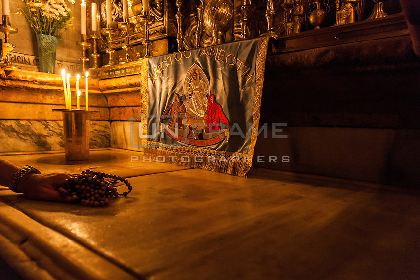 The Holy Sepulchre in the innermost chamber of the Aedicule, covered in medieval marble. Worshippers use to rub the stone with religious objects