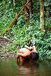 Yanomamo tribesman drinks from rain forest stream, Parima Tapirapeco National Park, Venezuela