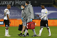 Andre Ayew of Swansea City (L) speaks to team mate Marc Guehi (R) is led away by team medical staff during the Sky Bet Championship between Swansea City and Luton Town at the Liberty Stadium, Swansea, Wales, UK. Saturday 05 December 2020
