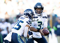 CHARLOTTE, NC - DECEMBER 15: Russell Wilson #3 of the Seattle Seahawks hands the ball off to Travis Homer #25 during a game between Seattle Seahawks and Carolina Panthers at Bank of America Stadium on December 15, 2019 in Charlotte, North Carolina.