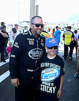 Jul. 20, 2014; Morrison, CO, USA; NHRA top fuel driver Shawn Langdon poses with a young race fan during the Mile High Nationals at Bandimere Speedway. Mandatory Credit: Mark J. Rebilas-