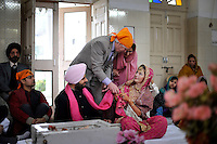 At the wedding ceremony of British/Punjabi couple Lindsay and Navneet Singh at a gurdwara in Amritsar, the bride's father attaches a pink scarf to the bride and groom.
