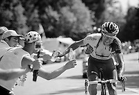 riders catch bottles offered by roadside fans to cool them down in the +35°C<br /> <br /> 2014 Tour de France<br /> stage 13: Saint-Etiènne - Chamrousse (197km)