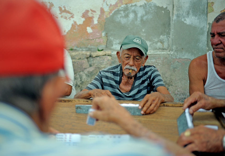 A 93-year-old man and his neighbours play dominos on a street corner in Santa Clara, Cuba. MARK TAYLOR GALLERY
