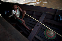 A boy sits in a boat at the docks in Rangoon (Yangon).