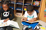 Education preschool 4 year olds boy and girl sitting near each other looking separately at picture books