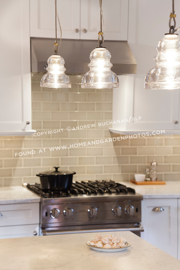 Pale green subway tile, Carrera marble countertops, and painted white cabinetry create a calm feeling in a newly remodeled kitchen.