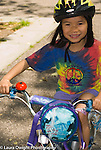 5 year old girl riding bicycle wearing safety helmet